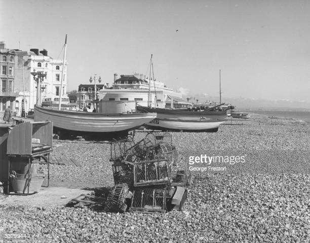 Fishing boats and equipment lie waiting for on the beach at Worthing Sussex