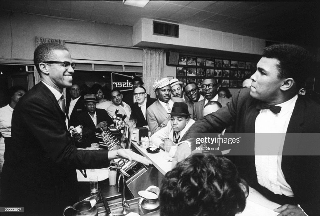 Black Muslim leader Malcolm X (L), behind soda fountain, with tux-clad Cassius Clay (now Muhammad Ali) (R), while surrounded by jubilant fans after he beat Sonny Liston for the heavyweight championship of the world.