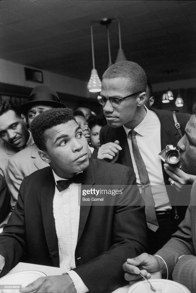 Black Muslim leader Malcolm X teasingly leaning on shoulder of tuxclad Cassius Clay who is sitting at soda fountain counter surrounded by jubilant...