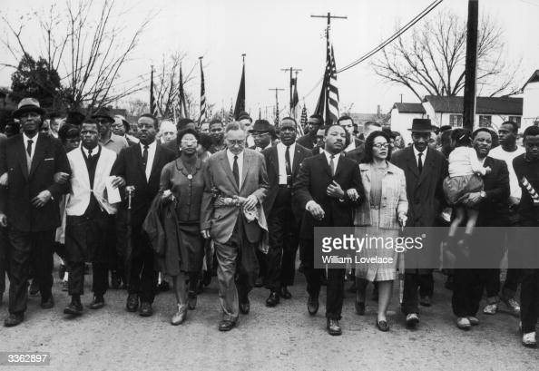American civil rights campaigner Martin Luther King and his wife Coretta Scott King lead a black voting rights march from Selma Alabama to the state...