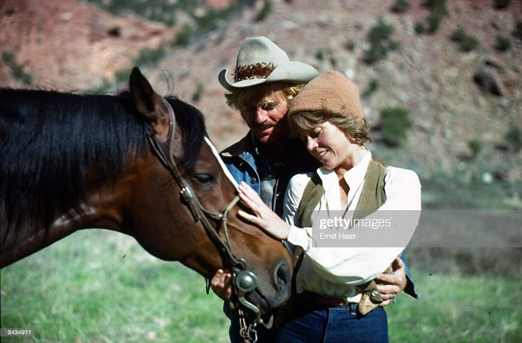 Film stars Robert Redford and Jane Fonda stroking a horse during the shooting of 'Electric Horseman' a Columbia/Universal production directed by Sydney Pollack.