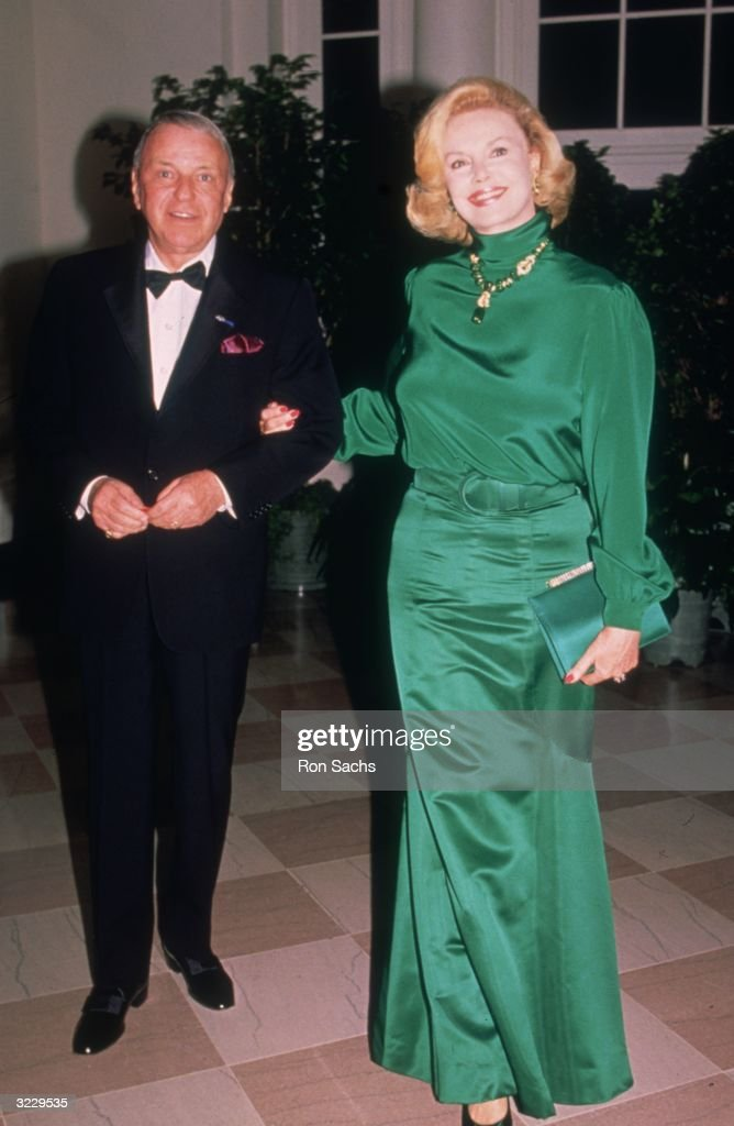 Full-length image of American actor and singer Frank Sinatra (1915 - 1998) posing with his fourth wife, Barbara Marx, outdoors at a White House State Dinner for Italian politician Giulio Andreotti, Washington, DC. Sinatra is wearing a tuxedo. Marx is wearing a long green gown.