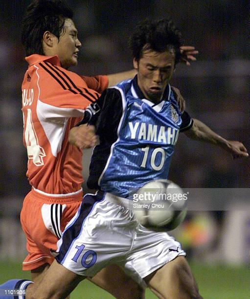 Toshiya Fujita of Jubilo Iwata Japan is fouled by Liu Jindong of Shandong Luneng China during the Asian Club Championship East Asia zone quarter...