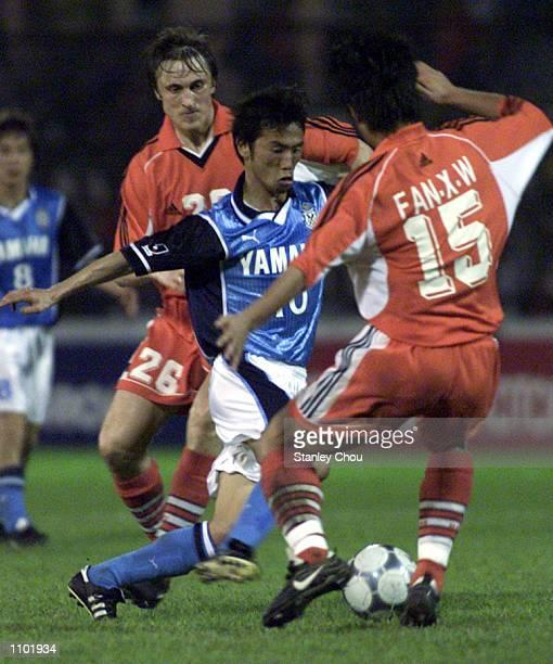 Toshiya Fujita of Jubilo Iwata Japan is sandwiched by Nagorniak Sergei and Fan Xuewei of Shandong Luneng China during the Asian Club Championship...