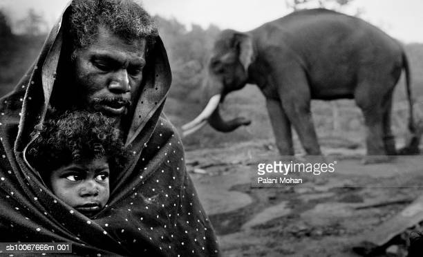 March 2002 A father and his daughter huddle under a blanket against the morning chill March 2002 at a logging camp in Top Slip southern India There...