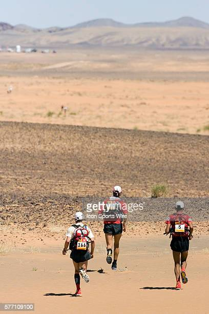 Lhoucine Akhdar of Morocco #314 Philippe Remond of France and Lionel Eveno of France run in erg Znaigui en route to check point 3 during fifth stage...