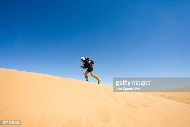 A runner climbs a dune in erg Znaigui en route to check point 3 during fifth stage of the 22nd Marathon des Sables between west of Kfiroun and erg...