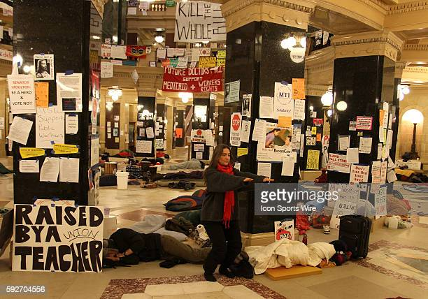 A woman does stretching exercises as protesters sleep in the state capitol rotunda on the 17th day protesting Wisconsin Governor Scott Walker's...