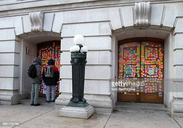 People pause to read hundreds of post it notes plastered on the staff entrance doors to state capitol in protest of Wisconsin Governor Scott Walker's...