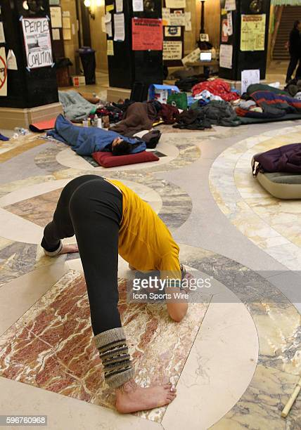 Protester Katie Kloth from Stevens Point Wisconsin practices yoga at the state capitol rotunda floor on the 17th day protesting Wisconsin Governor...