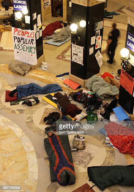 Protesters sleep in the state capitol rotunda floor as a law enforcement officer walks by on the 17th day protesting Wisconsin Governor Scott...