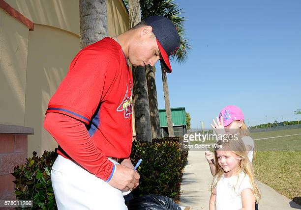 Aledmys Diaz signs autographs for young fans after being introduced to the media at the St Louis Cardinals spring training facility at Roger Dean...