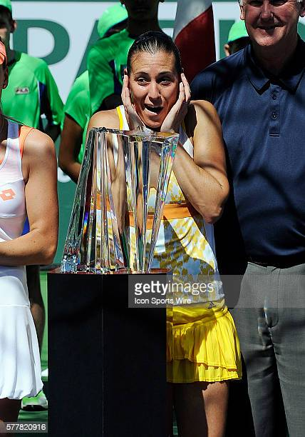 Flavia Pennetta on stadium one with the winners trophy reacts to the sound of streamers being launched in the air after defeating Agnieska Radwanska...