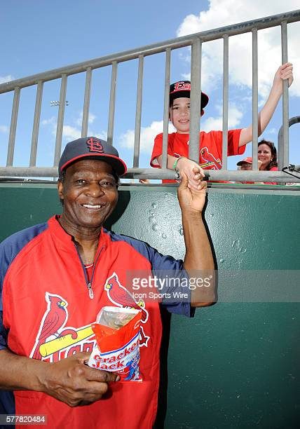 St Louis Cardinals Special Instructor Coach Lou Brock smiles after a young fan gives him a bag of Cracker Jack in the dugout during a MLB spring...