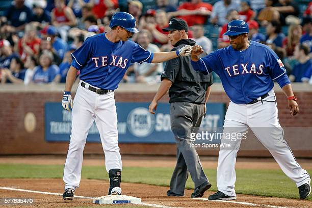 Texas Rangers shortstop Josh Wilson fist pumps first base coach Bengie Molina during the MLB spring training game between the Texas Rangers and...