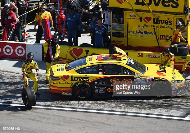 David Gilliland Front Row Motorsports Ford Fusion pulls into his pit box and bumps a tire belonging to Tony Stewart StewartHaas Racing Chevrolet...