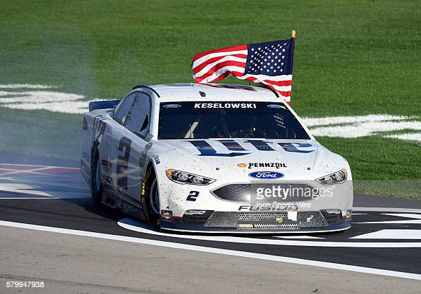 Brad Keselowski Team Penske Ford Fusion celebrates the victory with a cermonial burnout as he holds an American flag during the NASCAR Sprint Cup...