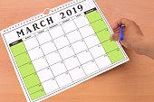 Hand holding blue felt tip pen and blank March 2019 calendar on wood desk