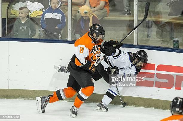 Rochester Institute of Technology Tigers defenseman Chase Norrish checks Minnesota State University Mavericks forward JeanPaul Lafontaine into the...