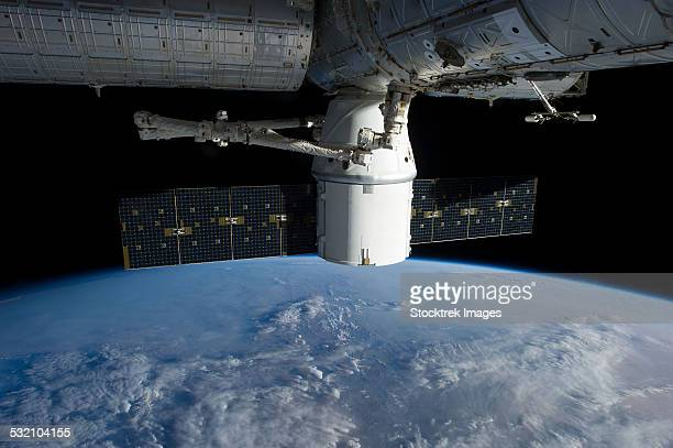 March 3, 2013 - The docking of a commercial cargo spacecraft to the International Space Station above a cloud covered Earth.