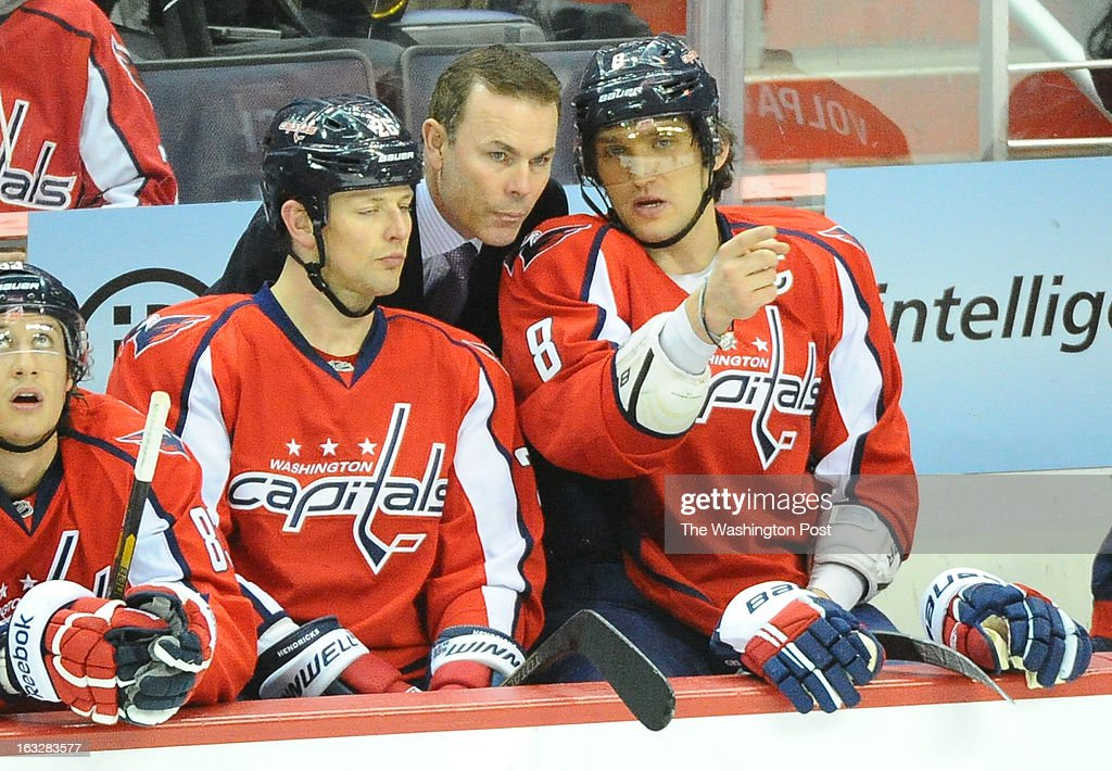 Washington Capitals head coach Adam Oates talks with Matt Hendricks (26) (L) and Alex Ovechkin (8) during a 1st period timeout against the Boston Bruins on March 5, 2013 in Washington, DC
