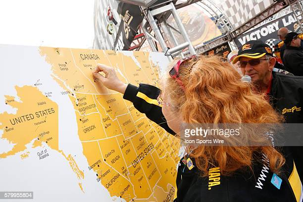 A fan in the South Point display booth in the Fan Engagement Area places a pin on a map of Canada prior to the NASCAR Sprint Cup Series Kobalt 400 at...