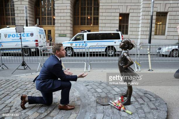 A man poses for a photo beside the 'fearless girl' statue facing the bronze bull statue near the Wall Street in New York the United States March 9...