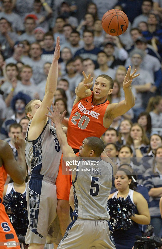 Syracuse guard Brandon Triche (20) passes the ball out after getting double teamed by Georgetown forward Nate Lubick (34) (L) and Markel Starks (5) during 2nd half action on March 9, 2013 in Washington, DC