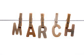 the month March in wooden letters on clothesline with wooden clothespins