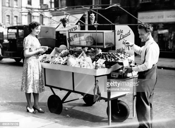 Marchand ambulant vendant fuits et légumes dans les rues de Londres RoyaumeUni le 20 août 1949