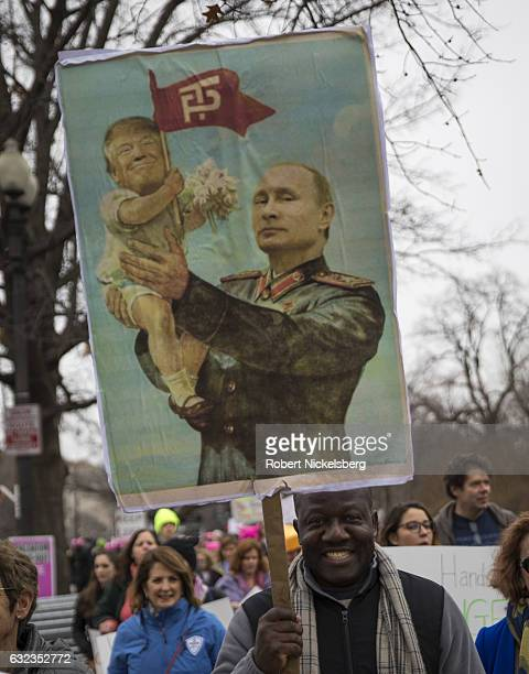 A marcher attending the Women's March on Washington carries a sign of Russian President Vladimir Putin holding up a baby image with a superimposed...