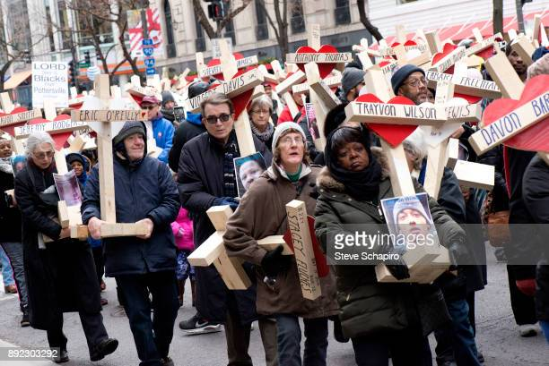 Marchers carry crosses as they participate in a march down Michigan Avenue honor of the city's more than 750 murder victims Chicago Illinois December...