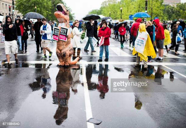 Marchers including a couple in TRex dinosaur costumes gather for the Science March down Constitution Avenue in Washington on Earth Day Saturday April...