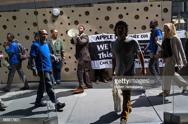 Marchers parade past an Apple Store April 15 2014 protesting Apple Inc's profits held in tax exempt overseas accounts in San Francisco California