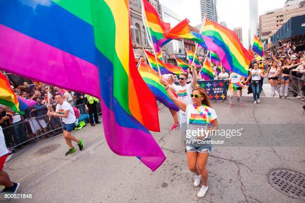 Marchers wave pride flags during the Pride Parade in Toronto Ontario June 25 2017 / AFP PHOTO / GEOFF ROBINS