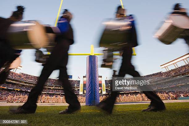 Marching band beside goal post in stadium at dusk (blurred motion)