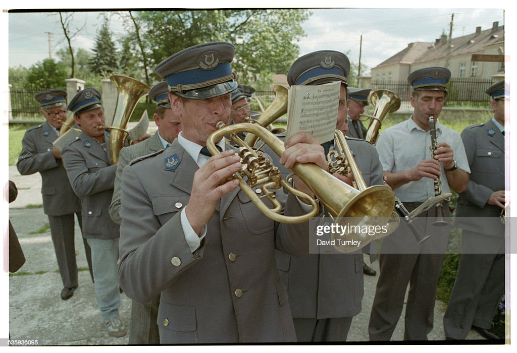 Marching band members play in a funeral procession down a road near Krakow, Poland. | Location: Near Krakow, Poland.