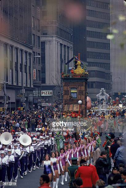 A marching band moves down the street followed by a Sesame Street float as crowds look on from the sidelines during the Macy's Thanksgiving Day...