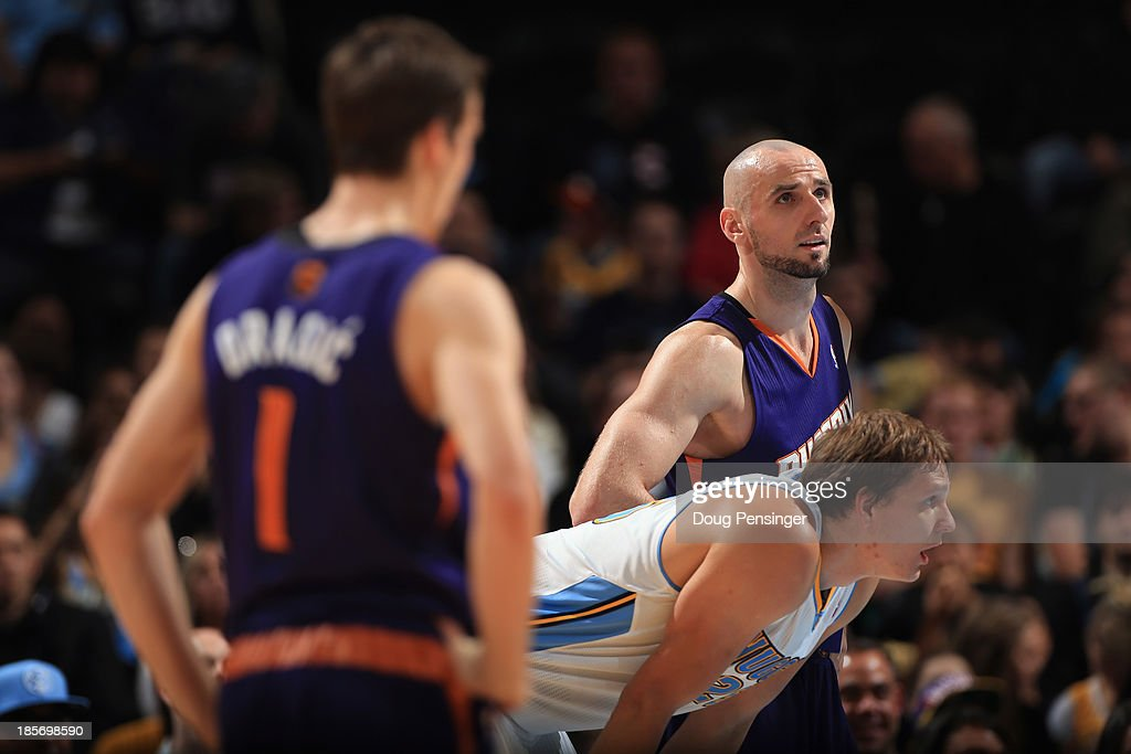 <a gi-track='captionPersonalityLinkClicked' href=/galleries/search?phrase=Marcin+Gortat&family=editorial&specificpeople=589986 ng-click='$event.stopPropagation()'>Marcin Gortat</a> (R) #4 of the Phoenix Suns awaits a free throw with <a gi-track='captionPersonalityLinkClicked' href=/galleries/search?phrase=Timofey+Mozgov&family=editorial&specificpeople=3949705 ng-click='$event.stopPropagation()'>Timofey Mozgov</a> #25 of the Denver Nuggets and <a gi-track='captionPersonalityLinkClicked' href=/galleries/search?phrase=Goran+Dragic&family=editorial&specificpeople=4452965 ng-click='$event.stopPropagation()'>Goran Dragic</a> #1 of the Phoenix Suns during preseason action at Pepsi Center on October 23, 2013 in Denver, Colorado. The Suns defeated the Nuggets 98-79.