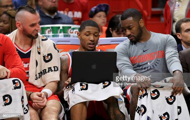 Marcin Gortat Bradley Beal and John Wall of the Washington Wizards look at a laptop during a preseason game against the Miami Heat at American...