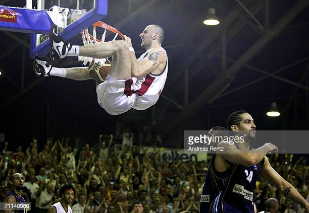 Marcin Gortat of Cologne hangs on after his slam dunk as Berlin's players Sharrod Ford and Luke Whitehead look on during game four of the Bundesliga...