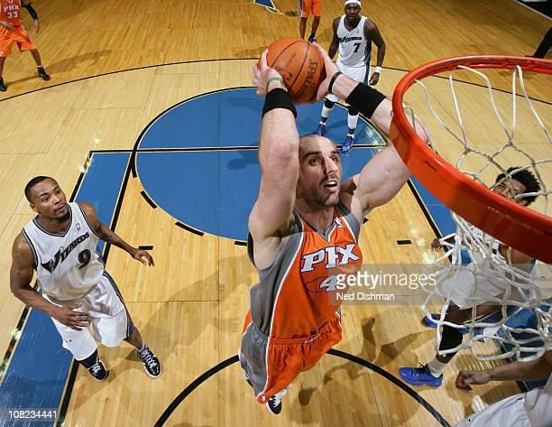 Marcin Gortat of the Phoenix Suns dunks against Rashard Lewis of the Washington Wizards at the Verizon Center on January 21 2011 in Washington DC...