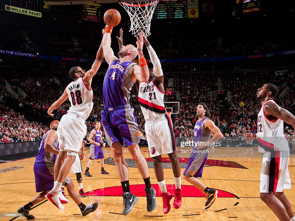 <a gi-track='captionPersonalityLinkClicked' href=/galleries/search?phrase=Marcin+Gortat&family=editorial&specificpeople=589986 ng-click='$event.stopPropagation()'>Marcin Gortat</a> #4 of the Phoenix Suns grabs a rebound against <a gi-track='captionPersonalityLinkClicked' href=/galleries/search?phrase=Nicolas+Batum&family=editorial&specificpeople=3746275 ng-click='$event.stopPropagation()'>Nicolas Batum</a> #88 and <a gi-track='captionPersonalityLinkClicked' href=/galleries/search?phrase=J.J.+Hickson&family=editorial&specificpeople=4226173 ng-click='$event.stopPropagation()'>J.J. Hickson</a> #21 of the Portland Trail Blazers on December 22, 2012 at the Rose Garden Arena in Portland, Oregon.