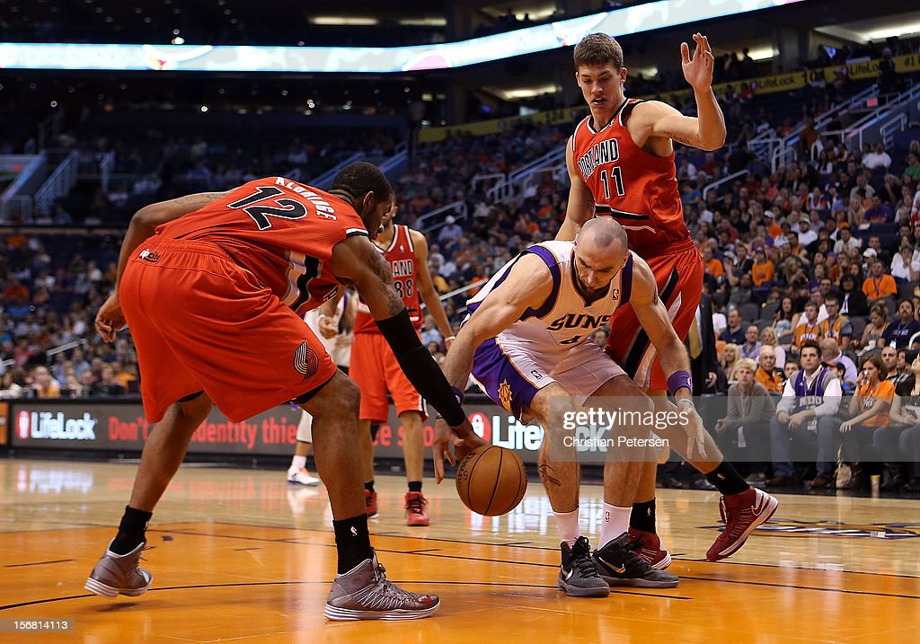 Marcin Gortat #4 of the Phoenix Suns reaches for a loose ball with LaMarcus Aldridge #12 of the Portland Trail Blazers during the NBA game at US Airways Center on November 21, 2012 in Phoenix, Arizona. The Suns defeated the Trail Blazers 114-87.