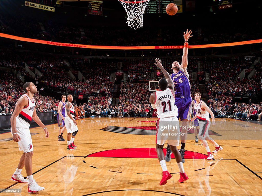 <a gi-track='captionPersonalityLinkClicked' href=/galleries/search?phrase=Marcin+Gortat&family=editorial&specificpeople=589986 ng-click='$event.stopPropagation()'>Marcin Gortat</a> #4 of the Phoenix Suns shoots in the lane against <a gi-track='captionPersonalityLinkClicked' href=/galleries/search?phrase=J.J.+Hickson&family=editorial&specificpeople=4226173 ng-click='$event.stopPropagation()'>J.J. Hickson</a> #21 of the Portland Trail Blazers on December 22, 2012 at the Rose Garden Arena in Portland, Oregon.