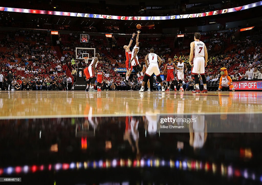 Marcin Gortat of the Washington Wizards and Hassan Whiteside of the Miami Heat jump ball during a preseason game at American Airlines Arena on...