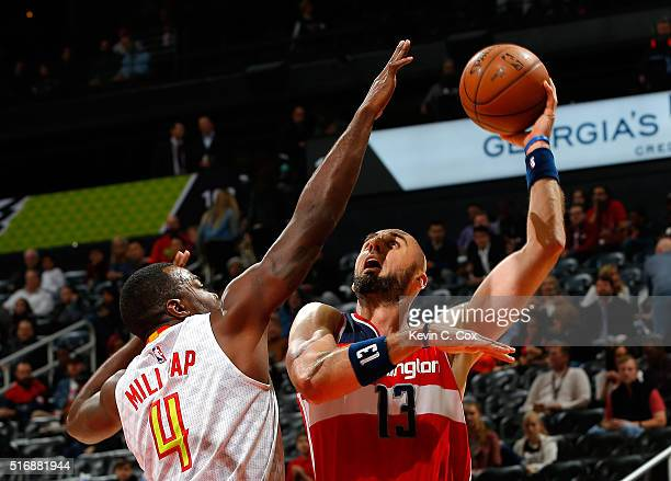 Marcin Gortat of the Washington Wizards attempts a shot against Paul Millsap of the Atlanta Hawks at Philips Arena on March 21 2016 in Atlanta...