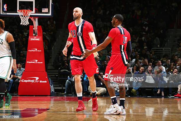 Marcin Gortat of the Washington Wizards high fives his teammate John Wall of the Washington Wizards during the game against the Boston Celtics on...