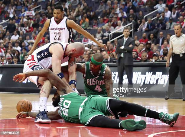 Marcin Gortat of the Washington Wizards scrambles for a loose ball against Amir Johnson and Isaiah Thomas of the Boston Celtics during Game Six of...