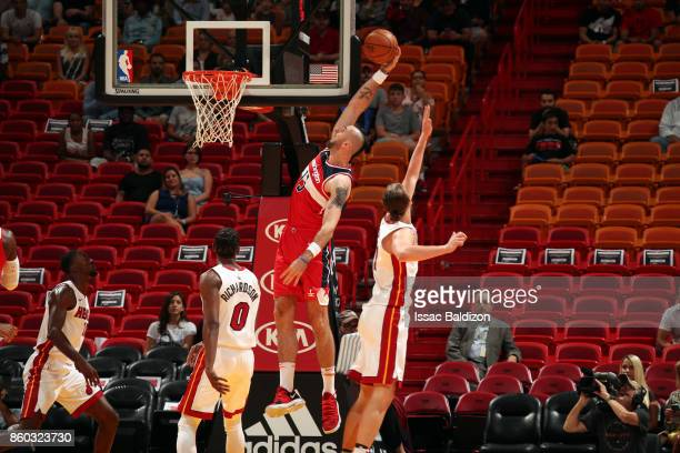 Marcin Gortat of the Washington Wizards shoots the ball during a preseason game against the Miami Heat at the American Airlines Arena on October 11...